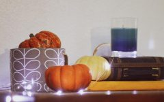 A table with small pumpkins, candles, and fairy lights on it.